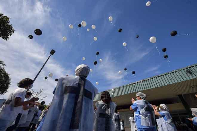 Kakitangan perubatan melepaskan belon ketika memberi penghormatan            kepada rakan sekerja yang meninggal dunia akibat COVID-19 di luar Hospital Universiti Sao Paulo di Sao Paulo, Brazil pada 12 Mei lalu. — Gambar AFP