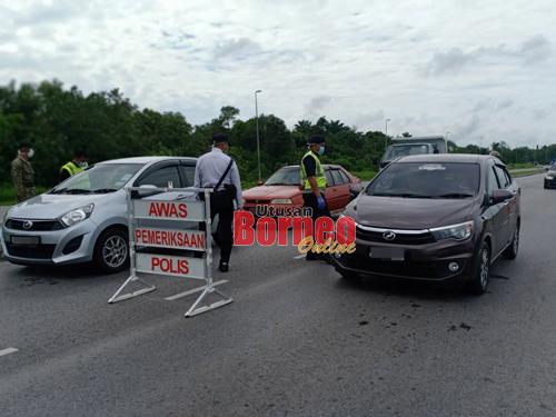 Petugas polis dan tentera memeriksa pengguna jalan raya semasa sekatan di Jalan Expressway Samarahan.