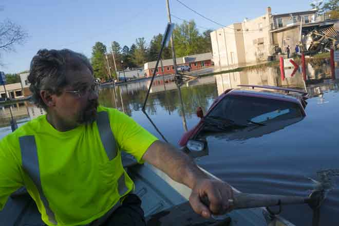 Seorang lelaki mendayung bot untuk memeriksa kerosakan di kawasan kejiranannya akibat banjir besar selepas empangan pecah di Sanford, Michigan kelmarin. — Gambar AFP