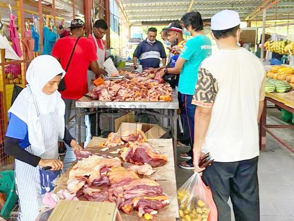 Pelanggan menungjungi jualan daging di Pasar Peladang.