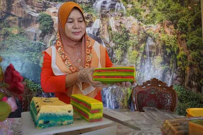 Rajemah Rose Awi menunjukkan kek lapis masam manis yang ditempah pelanggan ketika tinjauan di rumahnya di Kampung Bubor, semalam. — Gambar Bernama