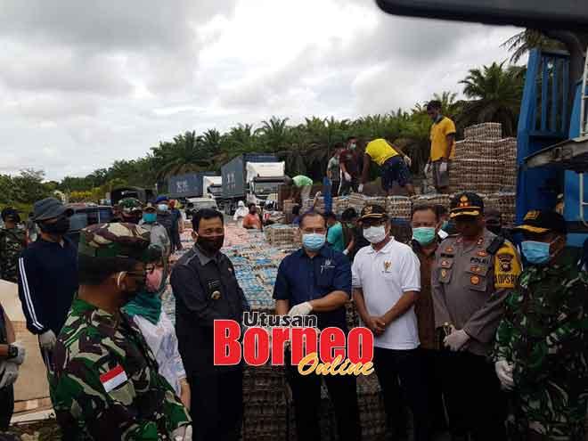 Indit (lima kanan) menyampaikan sumbangan kepada Bapa Adenan (dua kiri) untuk disalurkan kepada penduduk di Kalimantan Barat.