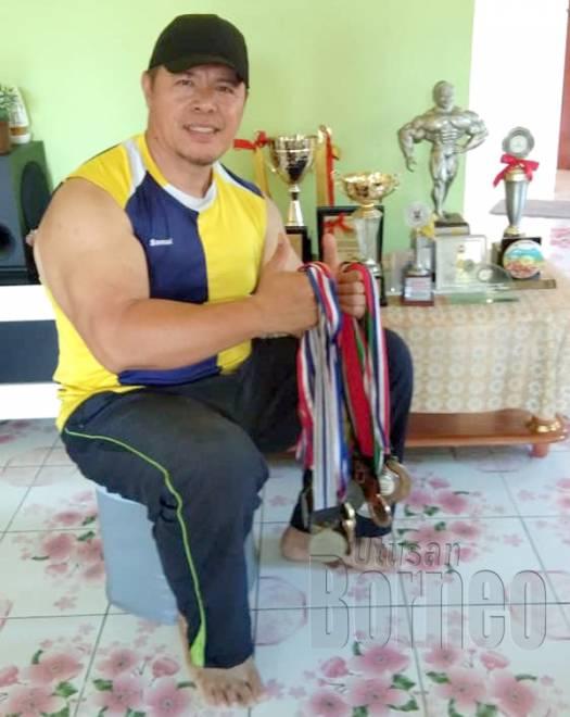 Gambar terbaharu Samad Lawi bersama medal dan piala yang dimenengi sepanjang bergelar atlet bina badan.