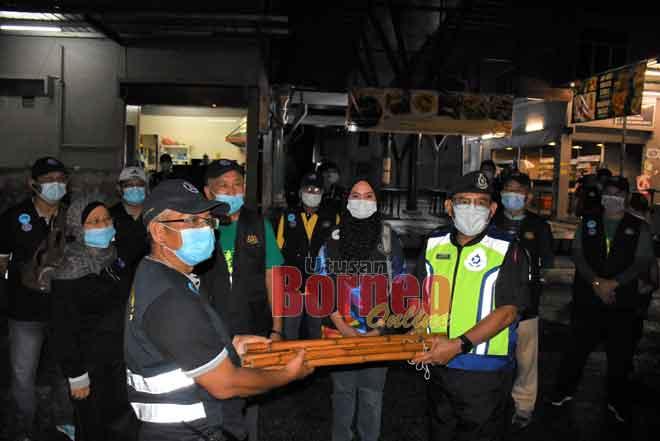 Ariffin (kanan) menyerahkan belantan buluh kepada Madehi sebagai simbolik pengaktifan semula SRS Kampung Nangka, Bandong dan Barieng malam kelmarin, sambil disaksikan (depan, dua dari kanan) Nurfatimah, Drahman dan yang lain.