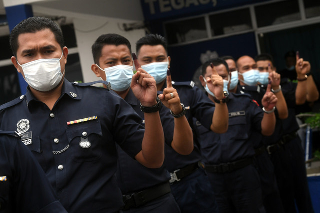Anggota polis menunjukkan jari yang ditanda dakwat kekal selepas mengundi awal bagi PRK DUN Chini di Balai Polis Chini hari ini. - Gambar Bernama