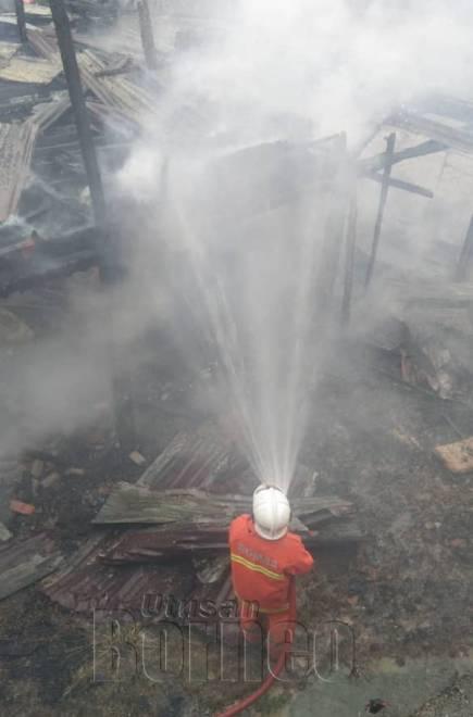 Anggota bomba menjalankan operasi pemadaman menggunakan sumber air daripada jentera.