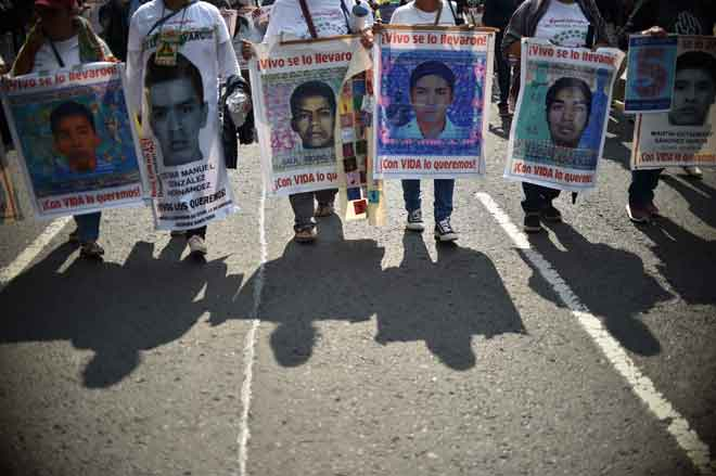 Gambar fail menunjukkan penunjuk perasaan membawa gambar sebahagian daripada 43 pelajar yang hilang semasa berdemonstrasi di negeri Guerrero pada 26 September, 2019. — Gambar AFP