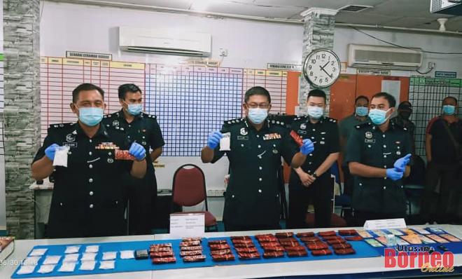 Lim (dua kiri) dan Sabri (kiri) masing-masing menunjukkan ketulan dadah jenis syabu yang berjaya dirampas daripada seorang lelaki dalam satu serbuan pada Isnin.