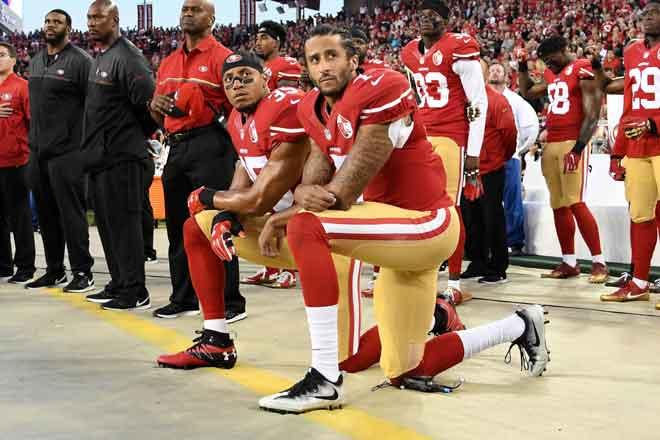 Gambar fail yang diambil pada 11 September 2016 ini menunjukkan Colin Kaepernick #7 dan Eric Reid #35 dari San Francisco 49ers berlutut sebagai tanda protes sewaktu lagu kebangsaan AS dimainkan sebelum perlawanan menentang  Los Angeles Rams di gelanggang NFL mereka di Levi's Stadium, Santa Clara, California. — Gambar AFP