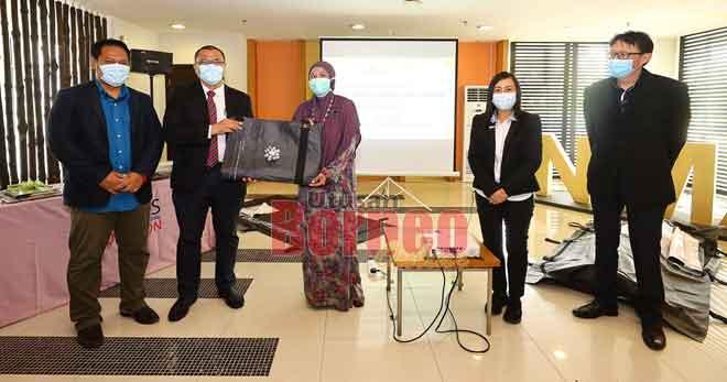 Wan Hashim (dua kiri) menyerahkan sumbangan beg jenazah kepada Dr Hayati sambil disaksikan tetamu kehormat lain.