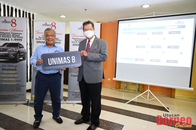 Kadim (kiri) menyerahkan plat kenderaan rasmi Unimas iaitu UNIMAS8 kepada Sulong semasa majlis pelancaran, yang diadakan hari ini.