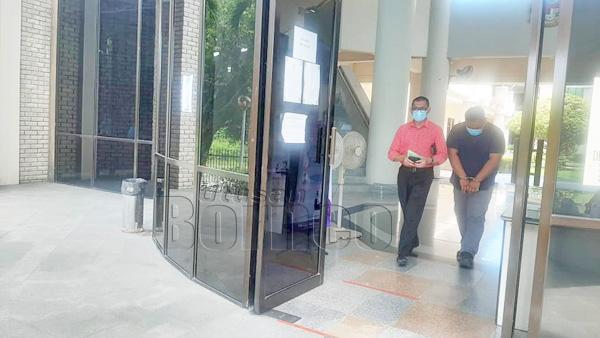 Supardi (kanan) dibawa keluar dari kamar mahkamah.