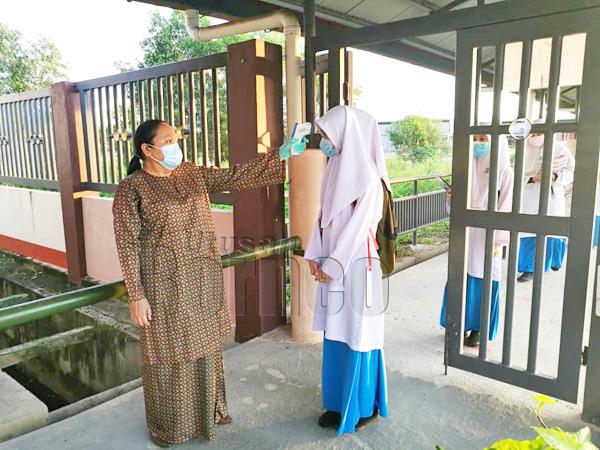 Salah seorang guru SMKPT membuat pemeriksaan suhu di pintu masuk sekolah.