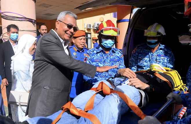 Mohd Redzuan (tengah) bersama Roslan (tiga kanan) melihat acara demonstrasi menyelamat dari pasukan Angkatan Pertahanan Awam ketika tiba bagi melawat Bilik Gerakan Bencana Negeri Johor, Pejabat Daerah Pertahanan Awam Johor Bahru, semalam. — Gambar Bernama