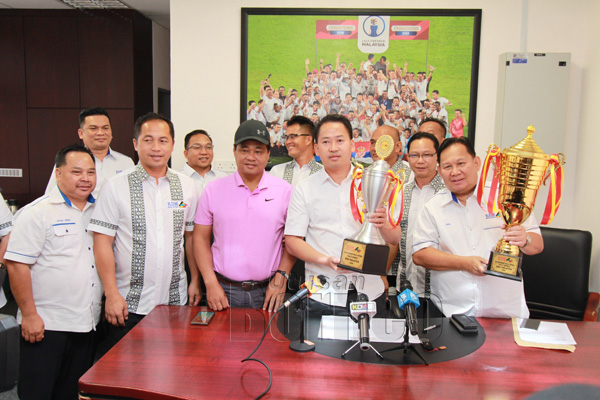 Peter (depan dua dari kanan) memegang piala yang ditawarkan untuk Piala Borneo KDM Malaysia 2020 semasa sidang medai di pejabat SAFA di Kota Kinabalu kelmarin. Turut bersama ialah jawatankuasa penganjur dan AMT KDM Malaysia.