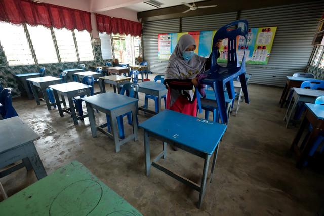 Guru kelas Tahun 6 Intan, Fatimah Azzahrah Amat Ramsa membersihkan semua kerusi dan meja para pelajar ketika tinjauan di Sekolah Kebangsaan Datuk Wan Kemara, Changlun di Kedah. - Gambar Bernama