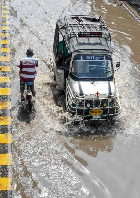 Seorang lelaki mengayuh basikal melintasi sebuah kenderaan ketika mengharungi banjir selepas hujan lebat                       di Amritsar, India kelmarin. — Gambar AFP