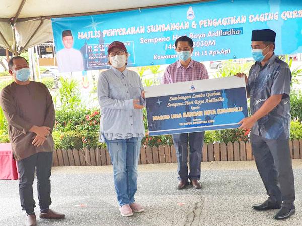 Christina menyampaikan sumbangan kepada wakil Masjid USIA Bandar Raya Kota Kinabalu.