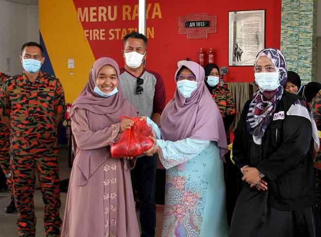 Pengerusi Nation Of Women (NOW) Haniza Mohd Talha (dua kanan) menyerahkan daging korban kepada wakil pelajar Ma'ahad Tahfiz Al-Quran dan Akademik Bakip, Nor Atiqah Syuhaidah Abdul Rahman (dua kiri) pada Majlis Korban Persatuan Suri dan Anggota Bomba Wanita Perak Bersama Nation Of Women (NOW) Perak Serta Kempen Keselamatan Kebakaran di Balai Bomba Meru Raya, Ipoh semalam. Turut sama Pengarah Jabatan Bomba dan Penyelamat (JBPM) Perak Azmi Osman (tiga kiri). — Gambar Bernama