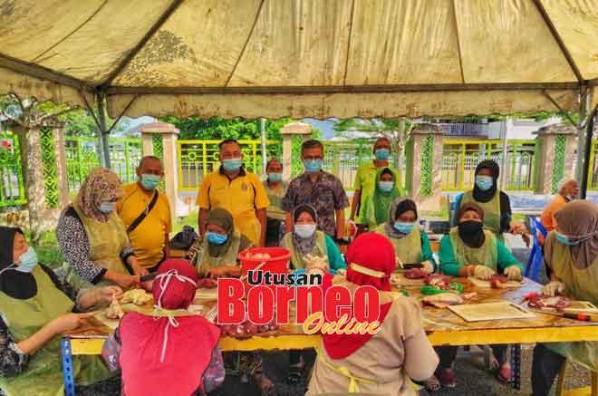 Dr Annuar (berdiri, tiga kiri) melawat stesen penyembelihan lembu korban di Jalan Bandong, Sibu semalam.