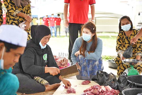 Vivian turut bersama-sama masyarakat Islam memotong daging lembu sebelum diagihkan.