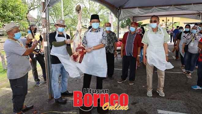 Dr Abdul Rahman melapah daging korban pada Program Ibadah Korban Peringkat DUN Pantai Damai.