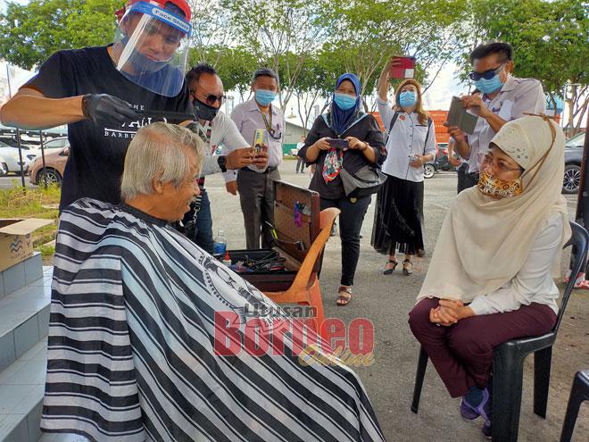 Fatimah (kanan) beramah mesra dengan salah seorang gelandangan yang menerima perkhidmatan gunting rambut percuma di Rumah MAKSAK Sibu semalam.
