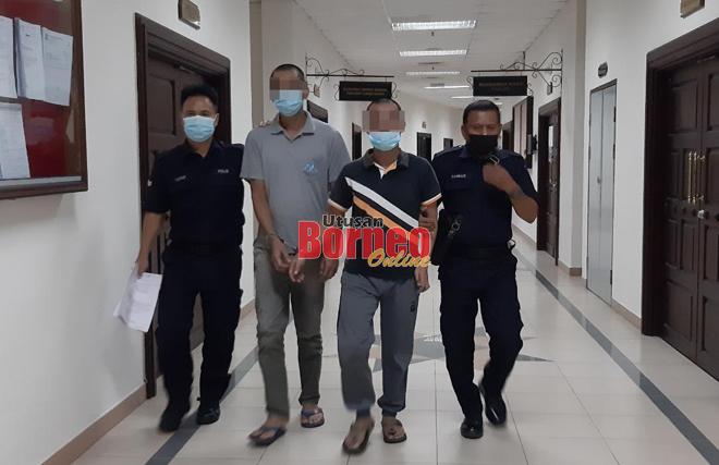 Tertuduh (dua kanan) diiringi polis di lobi Kompleks Mahkamah Kuching, hari ini.
