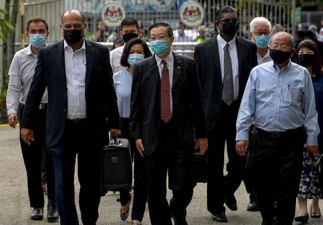 Lim diiringi peguamnya Gobind Singh dan RSN Rayer tiba di Mahkamah Sesyen Butterworth dekat Butterworth bagi menghadapi dua pertuduhan semalam. Turut hadir isterinya Betty Chew dan bapa Lim yang juga Ahli Parlimen Iskandar Puteri Lim Kit Siang. — Gambar Bernama