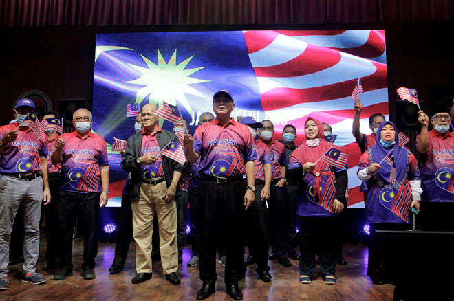Wan Rosdy (depan) bersama barisan kepimpinan kerajaan negeri Pahang mengibarkan Jalur Gemilang sambil menyanyikan lagu patriotik pada Majlis Sambutan Hari Malaysia 2020 Peringkat Negeri Pahang di Dewan Institut Kemahiran Belia Negara (IKBN) Pekan, semalam. — Gambar Bernama