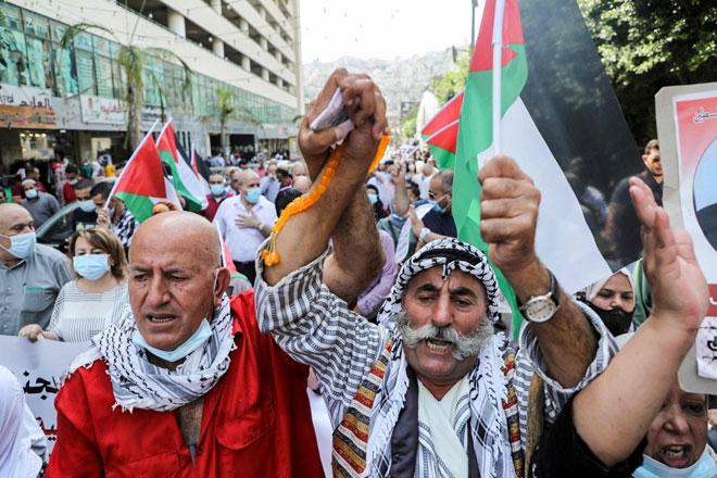 Penunjuk perasaan menjulang bendera Palestin ketika membantah keputusan                            Bahrain dan UAE untuk memulihkan hubungan diplomatik sepenuhnya dengan Israel di Nablus, wilayah Tebing Barat kelmarin. — Gambar AFP