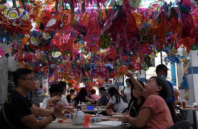 Pelanggan kelihatan cuba mengenali reka bentuk tanglung yang digantung di dalam restoran tersebut. — Gambar Bernama