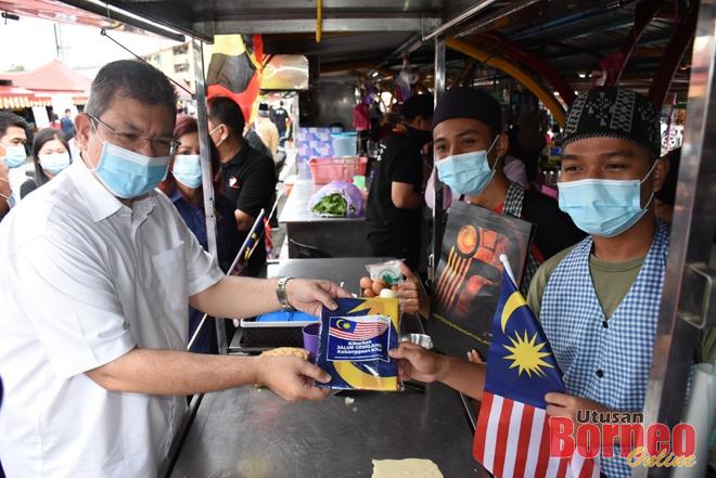 Saifuddin (kiri) mengagihkan Jalur Gemilang kepada salah seorang peniaga di Bandong Walk, hari ini.