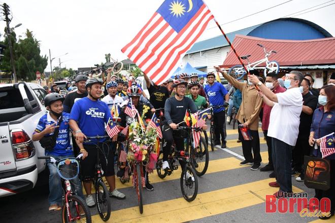 Saifuddin melakukan simbolik 'flag-off' program Kayuhan Santai Sempena Hari Malaysia 2020 yang diketuai oleh Dr Annuar (tengah).