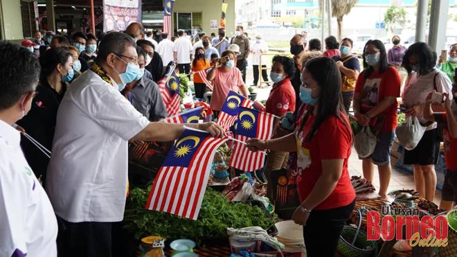 Saifuddin (kiri) mengagihkan Jalur Gemilang kepada peniaga di Market Sibu Jaya