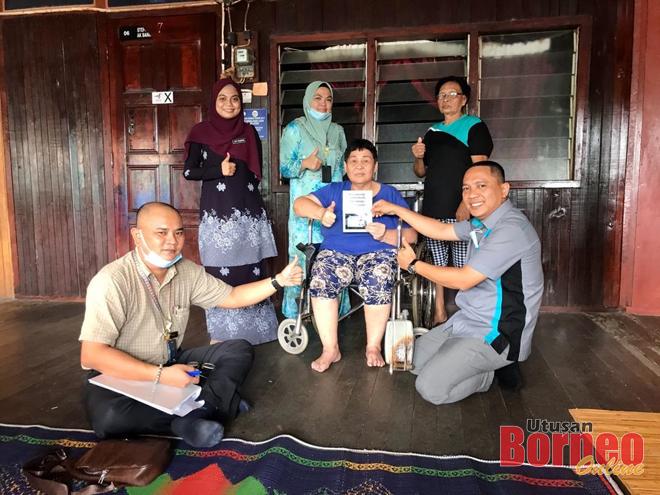 Mas Shamshuddin menyerahkan MyKad yang telah siap diperbaharui kepada Malaysia Andut sambil disaksikan Tuai Rumah Nyanyi (belakang, kanan) dalam operasi Mobile Ehsan JPN Sri Aman.