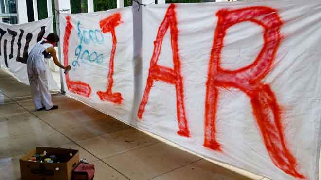 Seorang wanita Israel menyembur cat untuk menulis perkataan 'LIAR' (penipu) di kain rentang semasa demonstrasi                terhadap keputusan kerajaan menguatkuasakan semula perintah kawalan pergerakan bagi menangani peningkatan dalam kes COVID-19 di Tel Aviv kelmarin. — Gambar AFP