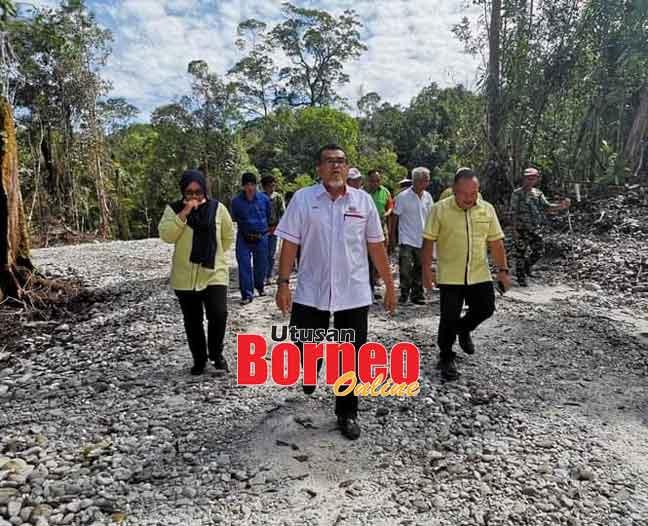Hasbi (tengah) ketika meninjau projek jalan Hulu Tubai ke Mentawai, Gunung Buda di Limbang semalam.