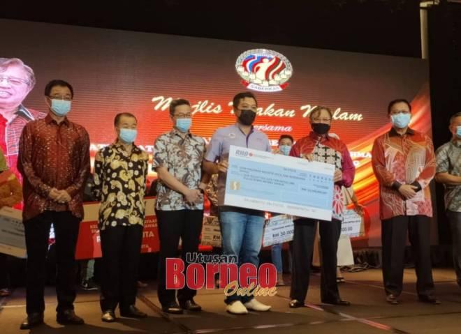 Abang Johari (dua kanan) menyerahkan SPIKS di bawah pelaksanaan SEDC berjumlah lebih RM23 juta kepada Ismandi Rambli yang mewakili 278 peserta, sambil disaksikan Abdul Karim (kiri sekali) dan yang lain.