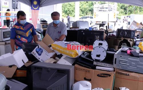 Hamzah dan Pengarah GVE Strategic Waste Sdn Bhd, Sim Yian Chai (kanan) melihat e-waste yang dikumpul pada kempen di Metro City, Matang hari ini. - Gambar Muhammad Rais Sanusi