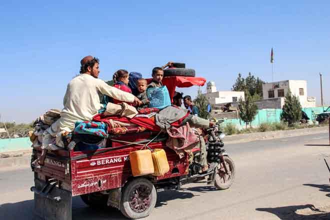 Penduduk bersama harta benda yang dapat dibawa bersama melarikan diri dari daerah Nadali ke Lashkar Gah di Helmand, kelmarin. — Gambar AFP