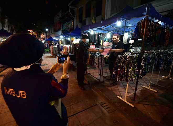 Anggota Majlis Bandaraya Johor Bahru (MBJB) mengedarkan notis pemberitahuan penutupan operasi Bazar Johor Bahru atau Bazar Karat  buat sementara waktu mulai semalam bagi mengekang penularan COVID-19 ketika tinjauan Bernama di Johor Bahru, semalam. — Gambar Bernama