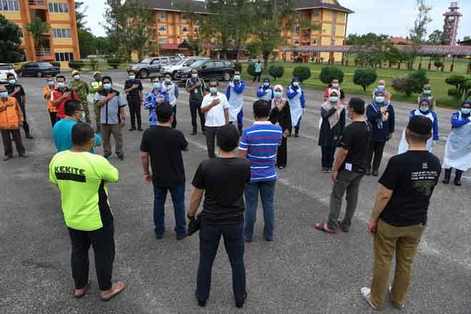 Ahmad Faisal  (tengah) bersama petugas barisan hadapan menerima ucapan penghargaan terima kasih daripada sekumpulan individu yang dibenarkan pulang ke rumah ketika tinjauan di pusat kuarantin, Akademi Bomba dan Penyelamat Malaysia, Wakaf Tapai dekat Narang, semalam. — Gambar Bernama