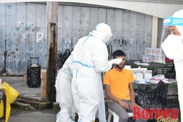 Petugas kesihatan menjalankan ujian swab COVID-19 ke atas penduduk dalam operasi ACD di Kampung Haji Baki, Kuching hari ini.