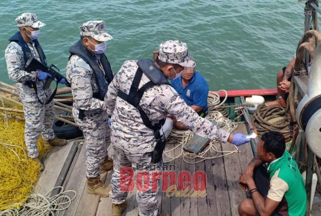Sekumpulan anggota APMM Sarawak memeriksa bot nelayan tempatan dan menyemak identiti kru serta mengambil suhu mereka.