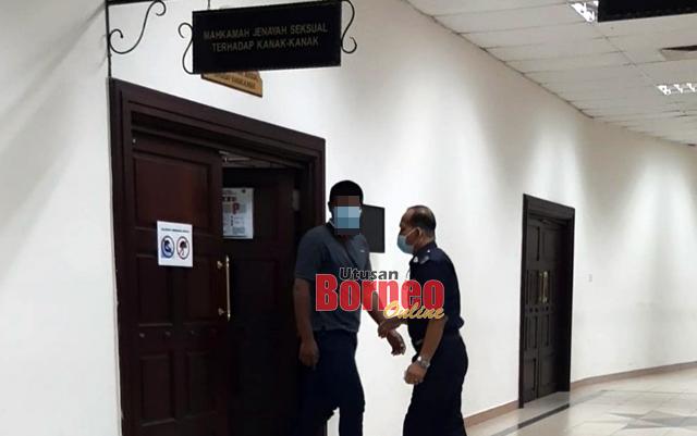 Tertuduh (kiri) keluar dari kamar mahkamah selesai jatuh hukum.