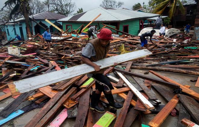 Seorang lelaki mengangkat papan untuk membaiki rumahnya yang ranap selepas                   Taufan Iota melanda Bilwi di Nicaragua kelmarin. — Gambar AFP