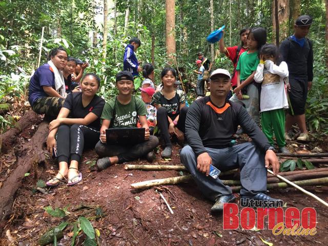 Sambau (duduk, kanan) dilihat bersama beberapa pelajar dan keluarga mereka semasa melakukan perjalanan tersebut baru-baru ini. -Gambar sumbangan Sambau