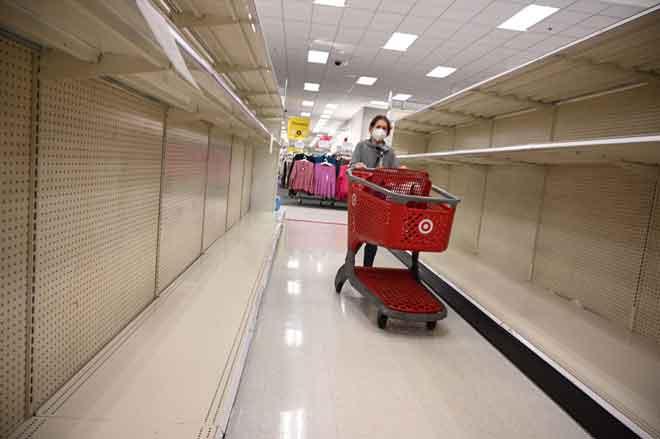 Seorang pelanggan menolak troli di sebelah rak kosong di sebuah pasar raya di Burbank, California kelmarin selepas pembelian panik menjelang pelaksanaan perintah duduk di rumah di negeri tersebut. — Gambar AFP