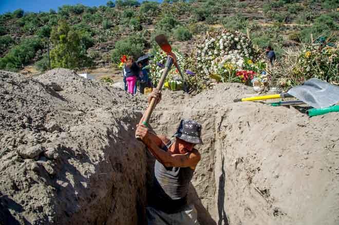 Pekerja menggali lubang di tanah perkuburan di Bandar Pantheon, Valle de Chalco kelmarin ketika Mexico dilaporkan mencatatkan lebih 100,000 kematian akibat COVID-19. — Gambar AFP